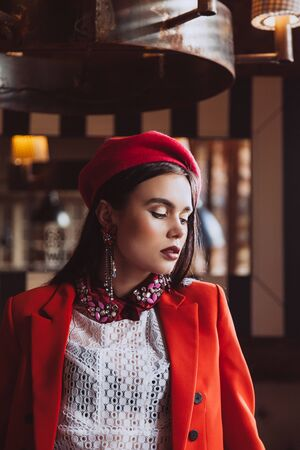 very beautiful brunette model with blue eyes in retro clothes: pink takes, white blouse, red jacket and skirt indoors