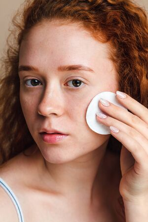 Young skin care concept. Attractive teenage girl with long red curly hair rubs her face with a cotton pad. No makeup, no retouching. Natural beauty.