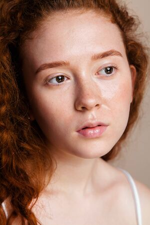 an attractive red-haired girl with brown eyes sprayed thermal water on her face. Sensitive skin care concept. Shot in a studio close-up, without makeup