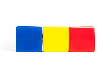 Rumania flag colors: blue, yellow, red in the form of children's cubes. On white background isolated with shadow