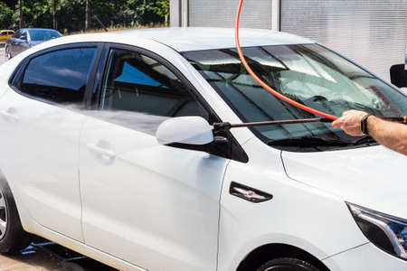 Rostov-on-Don, Russia - July 16, 2020: washing side mirrors of a white car at a self-service car wash