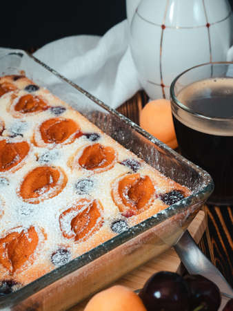 homemade curd cake decorated with icing sugar, slices of apricots and cherries in a glass form - still life, breakfast