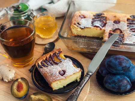 a square slice of plum pie on a round black antique plate, acacia honey, a vintage teaspoon and a cup of black tea Stok Fotoğraf