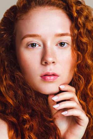 close-up portrait of a redhead girl with curly hair, small freckles and brown eyes. Beautiful model looks into the camera. The retouched photo was shot in the studio. Skin without makeup