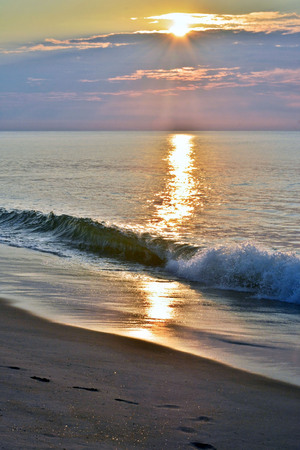 Golden and Glowing Seas Beneath a Summer Sunrise at the Shore Stock Photo