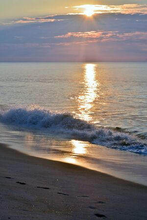 water wave: Golden and Glowing Seas Beneath a Summer Sunrise at the Shore Stock Photo