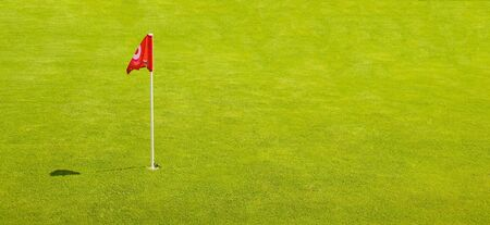 reg: A Reg Golf Flag on a perfect Grass putting green Stock Photo