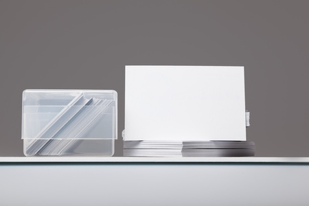 Blank Business cards to add own image in pile with box with cards in photo