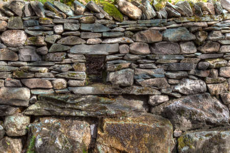 An old dry stone wall with drain to allow water through photo