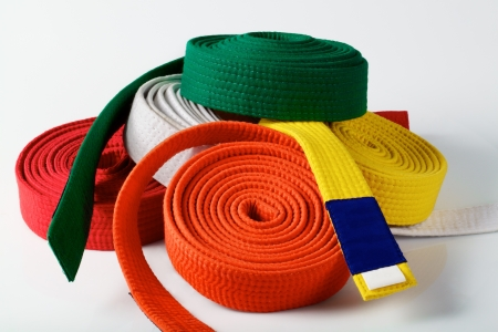 Coloured karate belts on white
