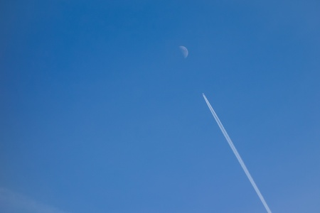 A plane and contrails heading for the moon photo