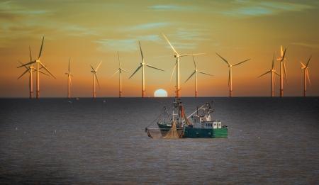windfarm: barco de pesca y las turbinas e�licas Foto de archivo