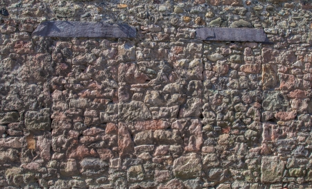 Wall of a castle with bricked up doorways photo