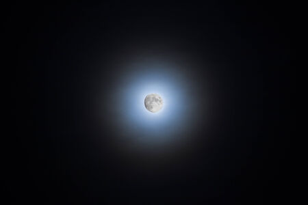 clouds making: Moon shining through clouds making a silvery blue halo Stock Photo