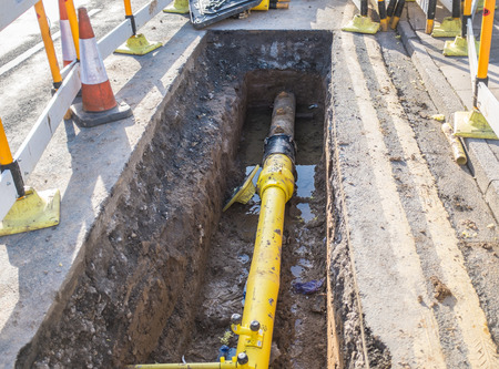 trench: Underground pipe being fixed in trench