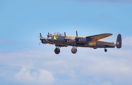 shuttleworth: CLEETHORPES, ENGLAND JULY 27TH: Lancster Bomber from Battle of Britain Memorial flight performs a fly past Cleethropes airshow on 27th July 2014 in Cleethorpes England.