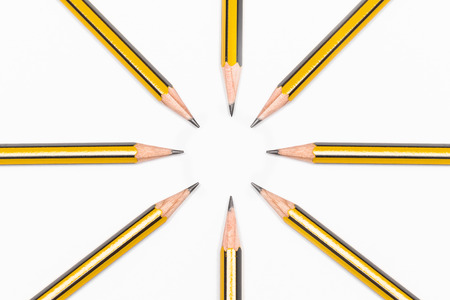 Pencils together forming patern on white paper background