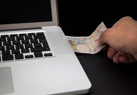 Cyber theft concept shot with laptop and money photo