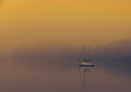 Boat on  a foggy Lake windermere Stock Photo