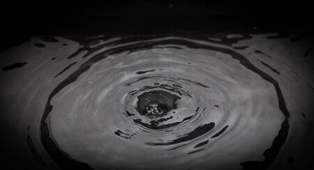 ripple effect: Close up of drop of water splashing in pool