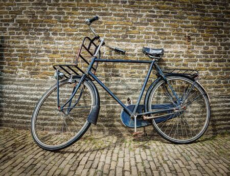Old fashioned bike leaning against a brick wall