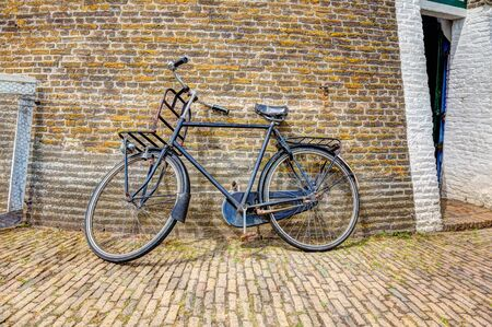 leaning against: Old fashioned bike leaning against a brick wall