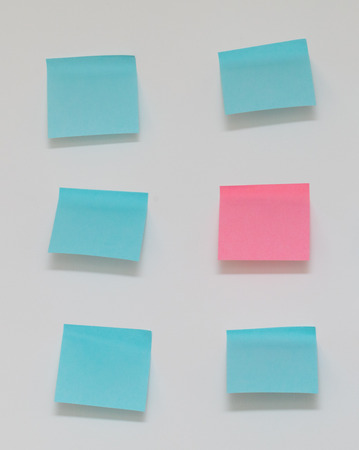 Single pink post it note in sea of blue post it notes Stock Photo