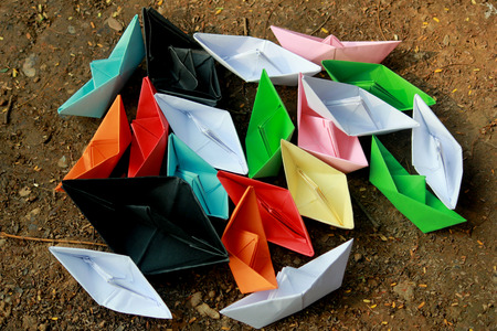barren land: Colorful paper boats on barren land Stock Photo