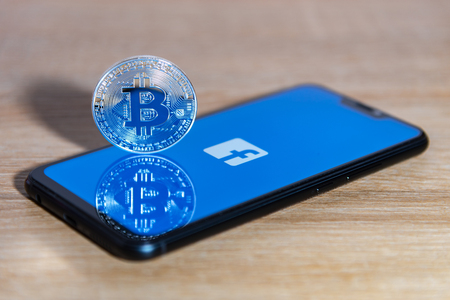 Bitcoin coin with the Facebook logo screen background
