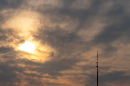 Silhouette view of antenna under twilight cloudy sky