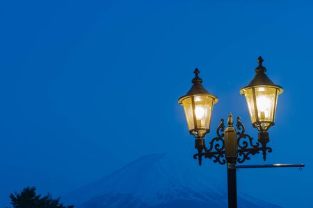 Close-up Street light and snow covered Mount Fuji (Mt. Fuji) with blue sky background at night.