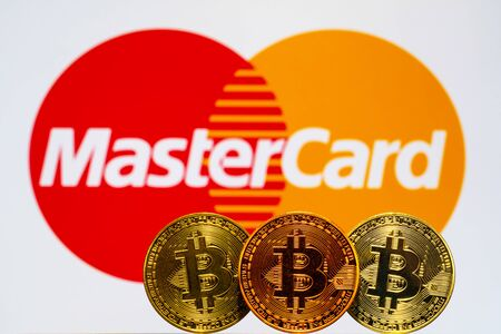 Gold Bitcoin coins with the MasterCard logo on background screen