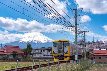 Fujikyu Railway train railroad track with snow covered Mount Fuji (Mt. Fuji) background in cherry blossoms springtime. Fujiyoshida City, Yamanashi Prefecture, Japan Фото со стока