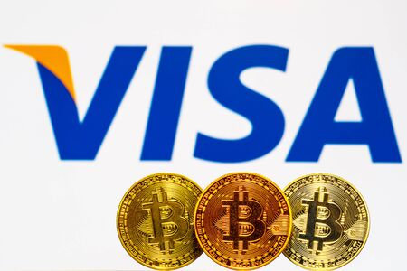 Gold Bitcoin coins with the Visa Plus System logo on background screen. A new type of business finance concept