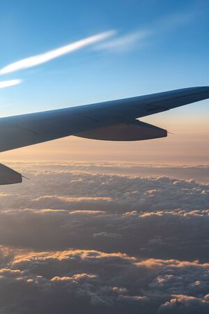 Up in the air, view of aircraft wing silhouette in dark blue sky horizon and cloud background in sun rise time. from viewed airplane window Banco de Imagens