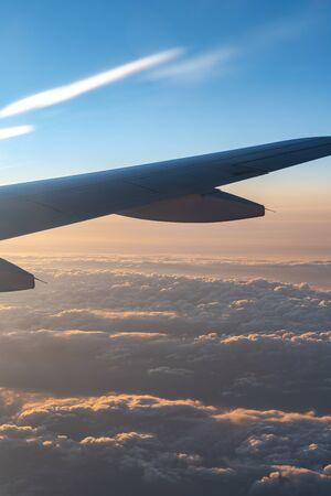 W powietrzu, widok sylwetki skrzydła samolotu w ciemnoniebieskim horyzoncie nieba i tle chmur w czasie wschodu słońca. z oglądanego okna samolotu Zdjęcie Seryjne