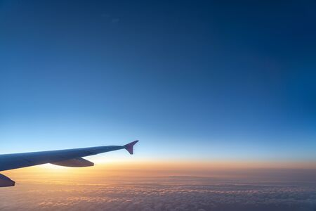 Up in the air, view of aircraft wing silhouette in dark blue sky horizon and cloud background in sun rise time. from viewed airplane window Stock Photo