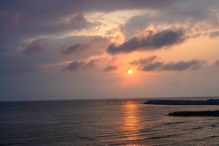 Colorful orange blue sky during sun set, gold sky sun clouds in evening Фото со стока - 128286780