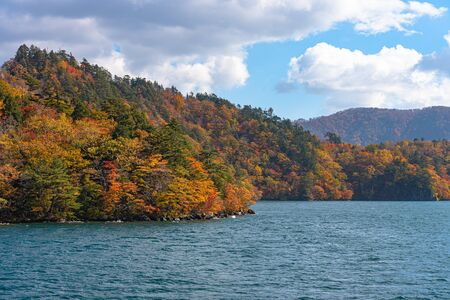 Beautiful autumn foliage scenery with Clear blue sky, water, white cloud at Aomori, Japan