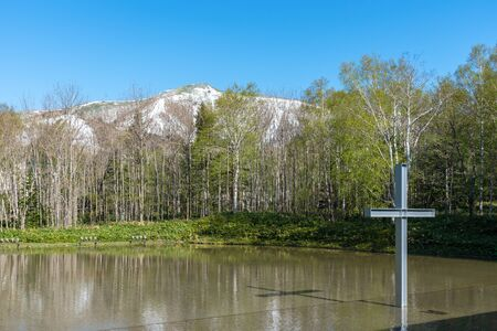Cross on the water with an inverted reflection in a beautiful nature forest mountain background 版權商用圖片