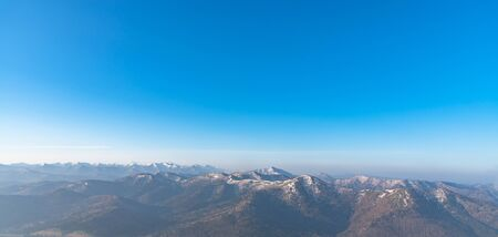 Panoramic view of beautiful mountain landscape, snowy mountain peaks covered by forest with a dark blue clear sky background in spring time sunny day