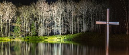 Cross on the water with an inverted reflection in a beautiful nature forest background. light up and illuminated the night