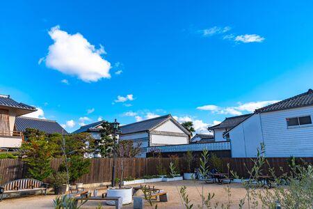 View of Kurashiki Bikan Historical Quarter. Townscape known for characteristically Japanese white walls of residences and willow trees lining banks of Kurashiki River , Okayama, Japan