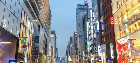 Night View of Ginza District, The District Has Famous Brand Flagship Stores Everywhere, Offers High End Retail Shopping. Text in Japan advertise stores name. Stock Photo