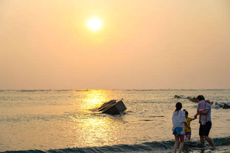 View from the beach with a yellow glowing sun setting in the horizon with an Asian family playing in the water. 報道画像