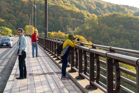 Aomori Prefecture, Japan-OCT 17, 2019: Tourists sightseeing on the Jogakura Ohashi Bridge during autumn foliage season. Towada hachimantai National Park.