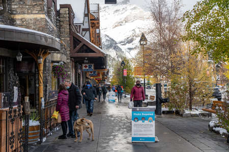 Street view of Banff Avenue in autumn and winter snowy season sunny day during covid-19 pandemic period. Banff, Alberta, Canada.