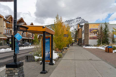Street view of Town of Banff. Bus stop in Banff Avenue in autumn and winter snowy season. Banff, Alberta, Canada. Editorial