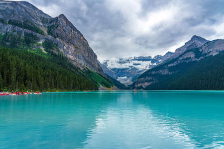 Lake Louise in sunmmer sunny day morning. Blue sky and white clouds reflected on the turquoise color lake water surface. Beautiful landscape in Banff National Park, Alberta, Canada.
