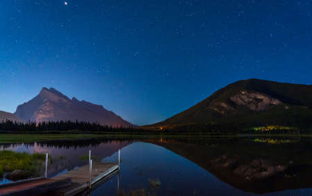 Vermilion Lakes Viewpoint at night, Full of stars above Mt Rundle, starry sky reflected in the water surface. Beautiful landscape in Banff National Park, Canadian Rockies, Alberta, Canada.